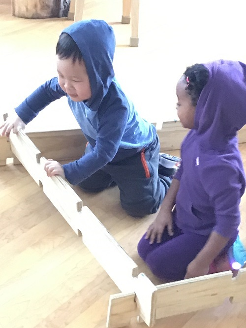 Preschool children working together to build with wooden planks