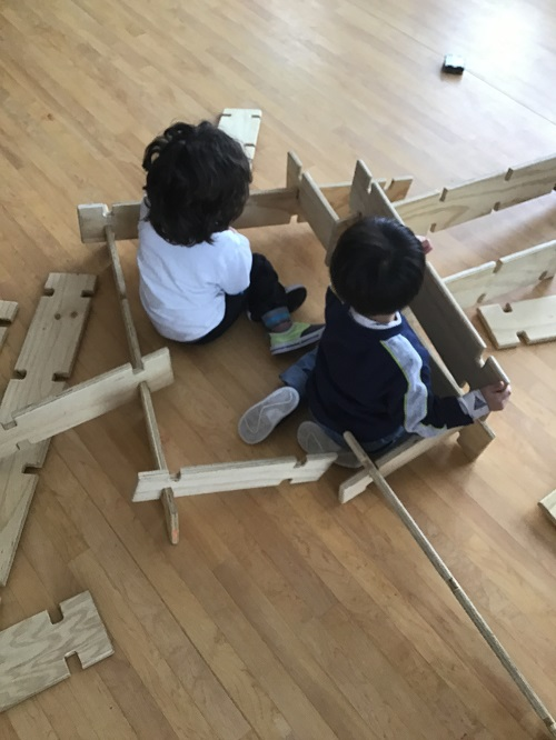 Two boys putting together wooden planks to build a structure