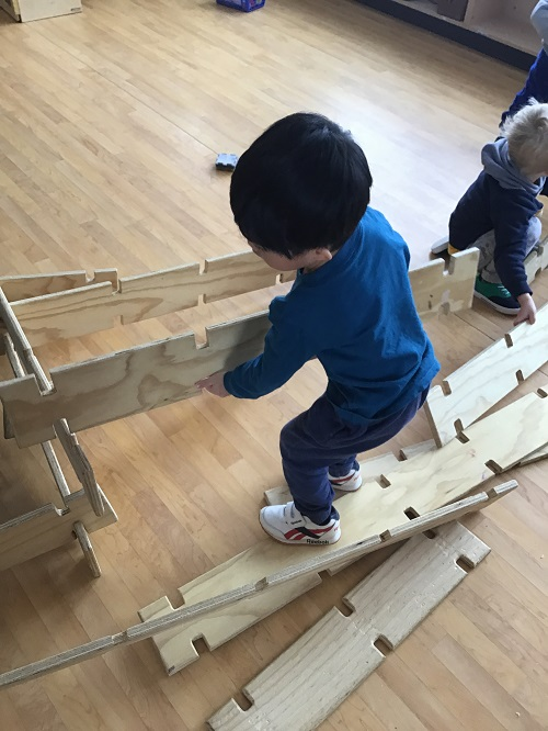 Preschool child building with wooden planks